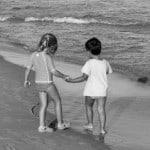 children-holding-hands-black-white-beach