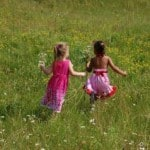 little-girls-playing-field-flowers-grass-image